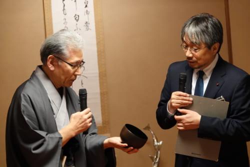 この日は、三浦雄一郎さんが標高8000mまで携行したものを手にしながら、このお椀にまつわるエピーソドを披露する室瀬和美さん(左)と、この催しの企画・演出・コーディネートを行なった小山薫堂さん(右)。