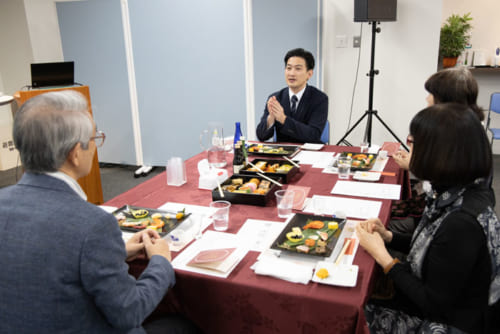 参加者の方と談笑しながら試食をする柳原さん(中央)