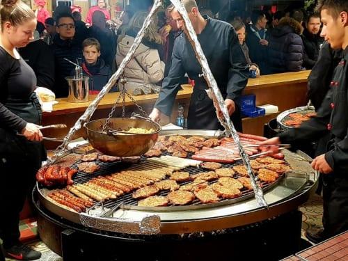 巨大なグリルで焼かれるソーセージやステーキ。