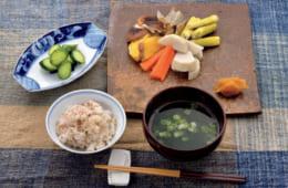 前列右から時計回りに、おつゆ(韓国製海藻・乾燥生姜・青葱)、雑穀ご飯、胡き瓜の浅漬け、温野菜サ ラダ(子芋・人参・さつまいも・椎茸・牛蒡・真菰筍・柚味噌)。韓国製海藻は娟卿(ヨンギヨン)夫人の実家から届く乾燥品。これに自家製の乾燥生姜を加え、熱々の出汁を注ぐ。温野菜は柚味噌をつけていただく。人参と真菰筍以外は田中泯さんの畑で取れたもの。真菰筍は、工房があることから定期的に訪れる鹿児島県奄美大島産だ。