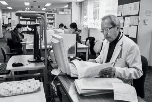 """訪問診療を終えて病院に戻ると、パソコンを使ってそれぞれの患者のカルテを手際よくまとめていく。「個々の患者の最後の希望に合わせていく""""オーダーメイド医療""""が理想でしょうね」"""