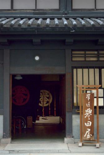 """『誉田屋源兵衛』の本社は、当代きっての宮大工・三上吉兵衛によって曾祖父の時代に10年かけて建てられたもの。大おお店だなの威厳が漂い、""""誉""""の一字に老舗の矜持が光る。"""