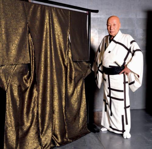非売品の帯や着物が並ぶ展示室で。非売の理由は、研究材料として後世に残すためだ。純金の粉を糸に付着させる技術革新に祝意を表して制作した、総薔薇文の純金の着物。源兵衛さんが着るのは、紬縮緬に破格子文様。