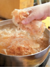 鍋の火は最小限までゆるめ、鮪節、鰹節を少しずつ振り入れる