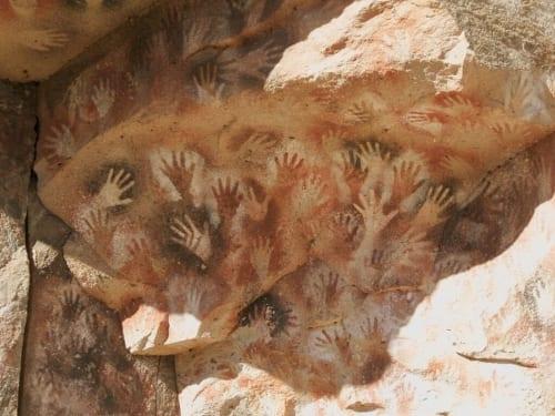"""グアムの洞窟で発見された色あざやかな手形壁画は15,000キロ以上離れたパタゴニア中部の先住民たちによって約9,000年前に描かれたといわれるクエバ・デ・ラス・マノスとよく似ているそうだ。画像引用:Created by modifying """" Hands"""" by MrHicks46 is licensed under CC BY-SA 2.0 (by is licensed under https://ccsearch.creativecommons.org/photos/39367ba4-8646-428d-97d1-d2fca7197cf8)"""