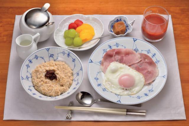 前列左から時計回りに、オートミール(酢漬けレーズン)、牛乳、砂糖、季節の果物(マスカット・苺いちご・缶詰の蜜み 柑かん)、梅干し、トマトジュース、ハムエッグ。 オートミールには牛乳と砂糖をかけていただく。缶詰の蜜柑が大好物で、一年を通して食卓に登場。トマトジュースは、高リコピントマトに林檎と生姜をブレンドした『カゴメ』の「トマトボーテ」を愛飲している。
