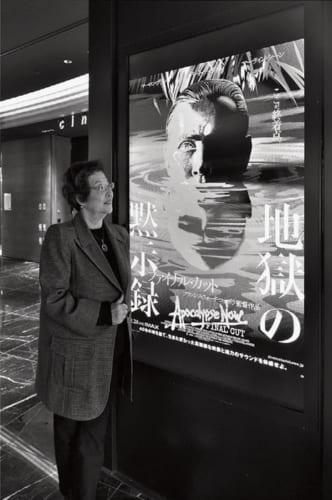 """『地獄の黙示録』ポスターの横で。「ひとつのフレームの中の絵が重層的で、観るたびに""""あっ、ここ見逃してた""""という発見がある。コッポラ自身も出演してます」"""