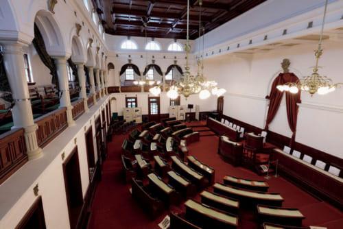 60人の議員が座れた旧議場も復元され、見学できる。天井からは、重量60kgのシャンデリアが5灯下げられている。
