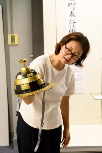敦賀の市街地を望む位置にある向出山古墳(写真上)と鉄地金銅装の復原甲冑を持つ奥村香子さん。