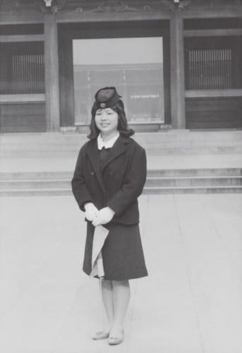 昭和37年4月、憧あこがれのバスガイドに。紺の制服姿の長谷井さんは19歳。時代につれ、制服も人目を引く赤やミニスカート等、より派手やかな色・デザインに変わったという。
