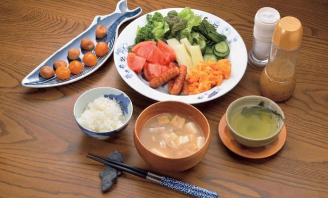 前列左から時計回りに、ご飯、キンカンの甘煮、梅干し、スクランブルエッグ、ウィンナーソーセージ、野菜サラダ(トマト・パセリ・サラダ菜・胡瓜・セロリ)、塩、フレンチドレッシング、煎茶・味噌汁(豆腐・油揚げ・長葱)。キンカンの甘煮は姉の手作りで、箸休めにつまむ。梅干しは塩分3%と低塩。野菜サラダには塩とフレンチドレッシングをかける。
