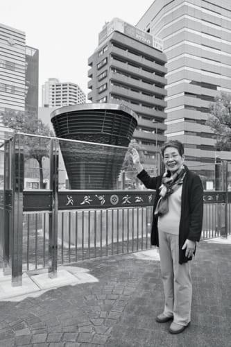JR川口駅前広場で。昭和39年に川口の鋳物師が制作した東京五輪の聖火台(写真)は、近く国立競技場に移設予定。「はとバスも前回の東京五輪では選手の送迎に大活躍でした」