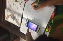 スマートフォンを見ながら、指示通りにノートに板書する