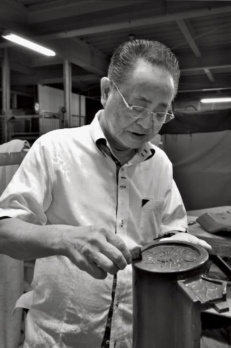 島袋瓦工場で生産する瓦は30種類。手にしているのは「在来役物瓦雄瓦(ざいらいやくものかわらおすかわら)」という伝統の瓦で、軒先の飾り物。プレス機で成型するが、仕上げは手作業で行なう。
