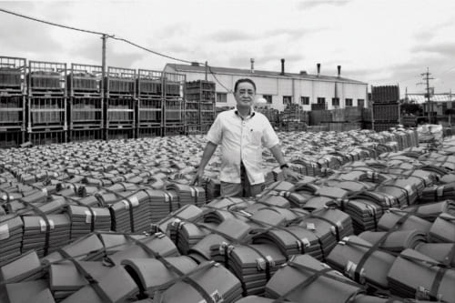 工場の敷地は3000坪。島袋さんが継いで以降土地を拡大した。出荷を待つ赤瓦。「納期を必ず守ることを心掛けてきました」。県内の店舗や企業のロゴが入った赤瓦の注文も。