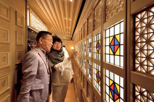 職人が手がけた、福岡県大川市の組子細工の見事さに見入る山本夫妻。通路にも、乗客を楽しませる工夫が満ちている。