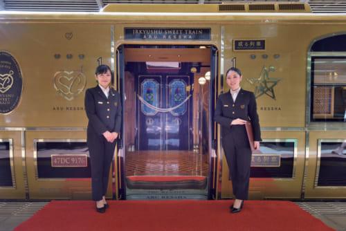ホーム上に赤絨毯が敷かれ、客室乗務員が乗降口で乗客を迎える。最上級の出迎えに旅への期待が一気に高まる。