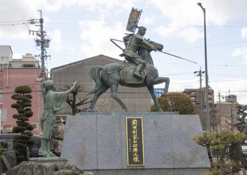 利家の出身地・荒子(愛知県名古屋市)に立つ前田利家公初陣之像。まつが手を振って見送る。