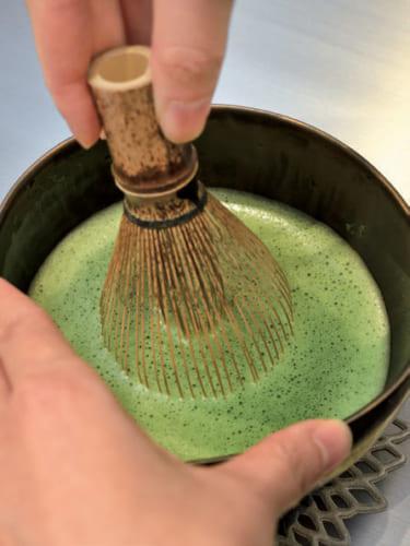3.縦に大きく茶筅を動かし抹茶が泡立ってきたら、表面を撫でるようにM字状に動かす。